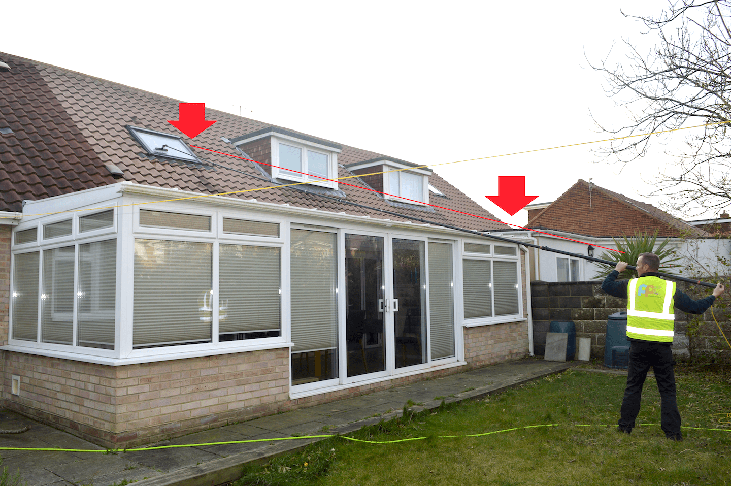 cleaning windows over a conservatory